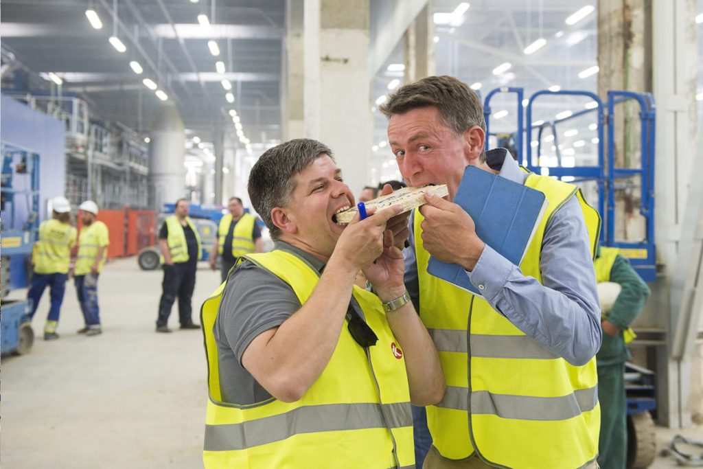 """Kázmér Szilárd (balra) és Hendrik Hecht (jobbra), ügyvezető igazgatók """"ráharapnak"""" az első OSB-lap egy darabjára az Interspan Faipari Kft. új üzemében, Vásárosnaményban 2016. június 8-án. A 30 milliárd forintos beruházásból felépített gyárban évi 300 ezer köbméter OSB-lapot tudnak gyártani."""